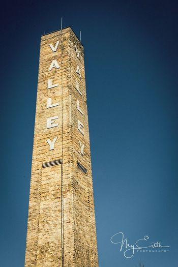 Tall - High Built Structure Text Architecture Tower Smoke Stack Chimney Clear Sky Communication Blue Building Exterior Day No People Outdoors Skyscraper Sky Clock