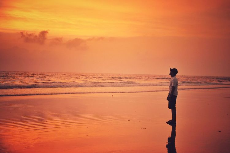 Man standing at beach during sunset