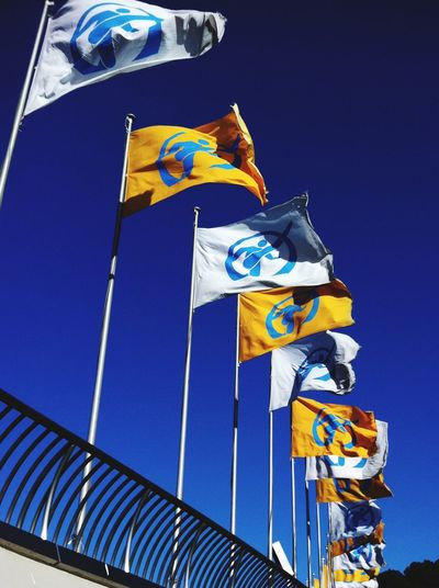 Low angle view of waving flags against clear blue sky