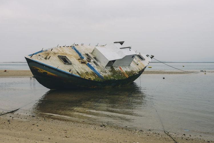 Abandoned Ship Moored At Beach