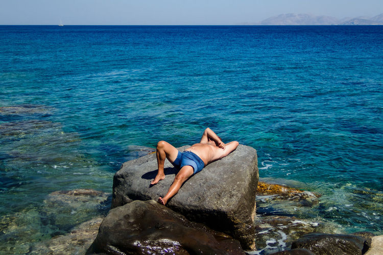 Man relaxing on rock by sea against sky