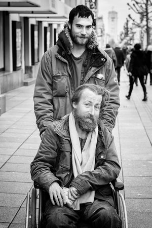 """Logan and Jack were walking down the city's main street. It was obvious that a lot of people were looking at them – after they had passed them. I suppose I was one of them. But I turned around and caught up with Logan and Jack. I've made it my rule to always ask about the photo right at the beginning of an encounter. It didn't seem right with Logan and Jack, though, so I started by asking what they were doing before asking for the photo. Logan laughed and bent over to his friend Jack in the wheelchair: """"He wants to take our photo. What do you say, are we going to allow that?"""" The tone in his voice already suggested they'd agree. So, meet Logan and Jack. Logan's name isn't Logan, but he told me I should use that instead. """"Like Wolverine, you know"""", he said. Logan and Jack have been friends for more than a year now. Jack lives in a small room in a homeless shelter. Logan still has his own little flat, but expects eviction any day now. He plans to go to an emergency shelter for the time being. """"You know, this spreading inhumanity is what really scares me. Just this morning someone accidentally kicked my begging cup and all the coins were running over the street. You'd think someone would stop. But no, all those people just kept moving on. And by now, I'm being harassed or even arrested by the police every other day. I don't know, maybe I'll just leave. Go to Spain or South America. But neither do I want to let them drive me off."""" Bum Friend Friends M Stranger Wheelchair The Portraitist - 2016 EyeEm Awards"""