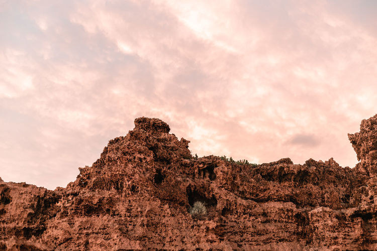 Low angle view of rock formations against sky during sunset