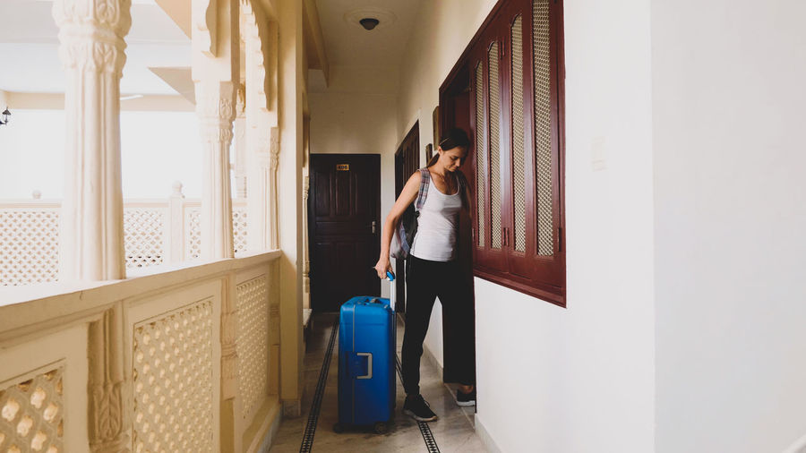 Woman locking door while standing by suitcase at hotel