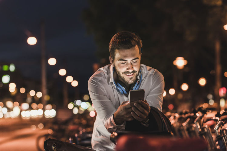 Young man using mobile phone at night
