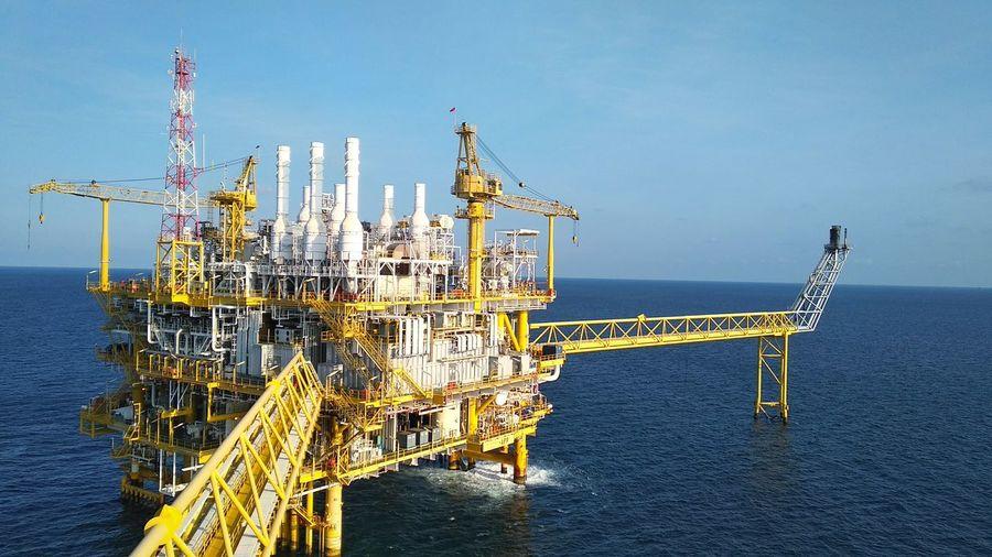 Offshore platform in sea against blue sky