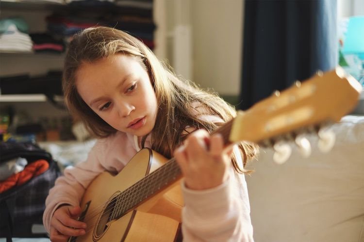 Close-up of girl playing guitar at home