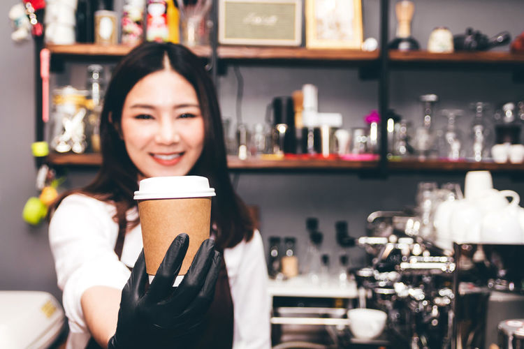 Barista holding coffee in coffee shop Adult Beautiful Woman Black Hair Business Coffee Coffee - Drink Coffee Cup Cup Drink Food And Drink Glass Hairstyle Holding Indoors  Mug One Person Portrait Real People Refreshment Women Young Adult Young Women