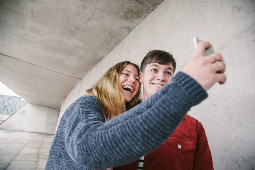 Young Cute Couple having fun while taking weird Seflies with their Smartphones in Berlin Berlin City Couple Fun Happy Real Red Young Boy Concrete Couple - Relationship Cute Enjoying Life Girl Grey Lifestyles People Positive Emotion Real People Selfie Smartphone Teenager Togetherness Urban Young Adult