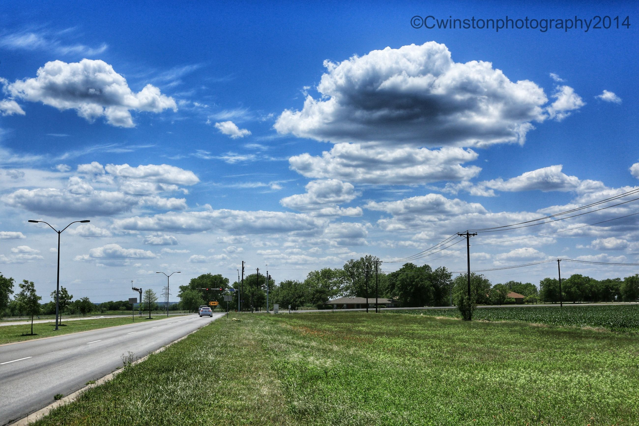 sky, field, grass, landscape, road, cloud - sky, transportation, blue, tranquility, tranquil scene, cloud, tree, the way forward, nature, rural scene, scenics, country road, green color, grassy, electricity pylon