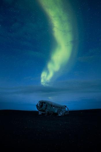 Aurora borealis over abandoned airplane at night