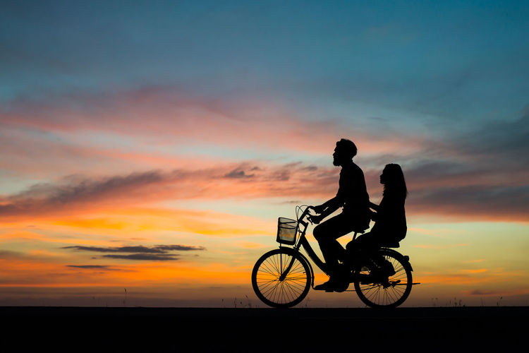 Silhouette man and woman on bicycle against sky during sunset