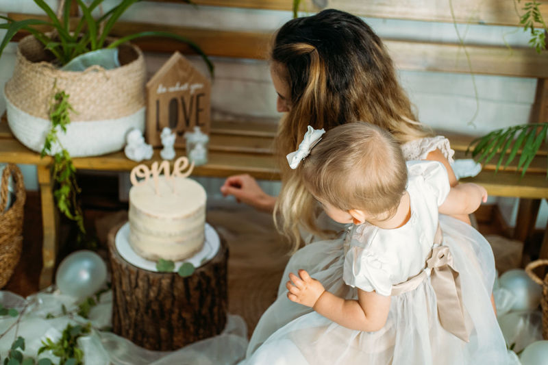 High angle view of mother with daughter looking at cake