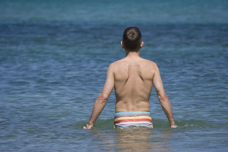 Rear View Of Shirtless Man At Sea