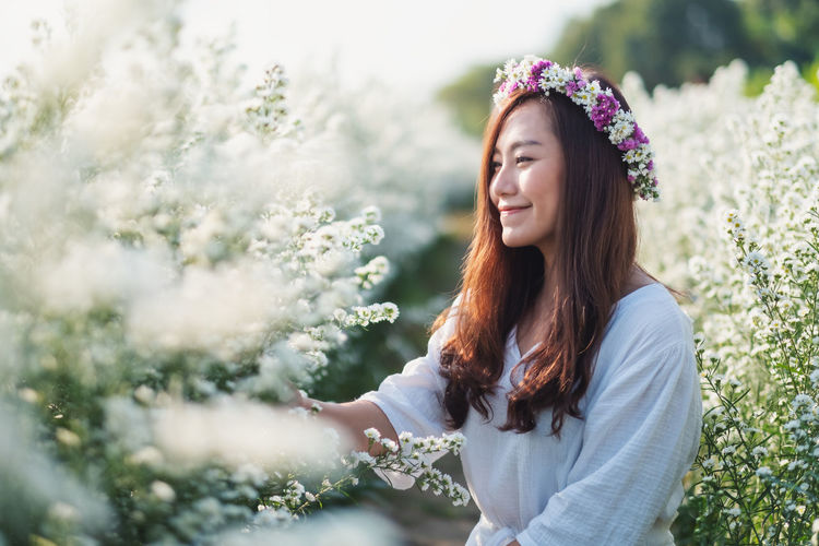 Smiling woman standing by flowering plants