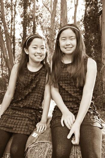 Portrait of teenage siblings sitting on field