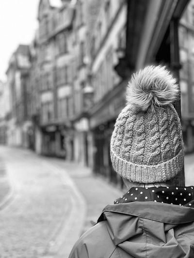 Rear view of woman walking on street in winter