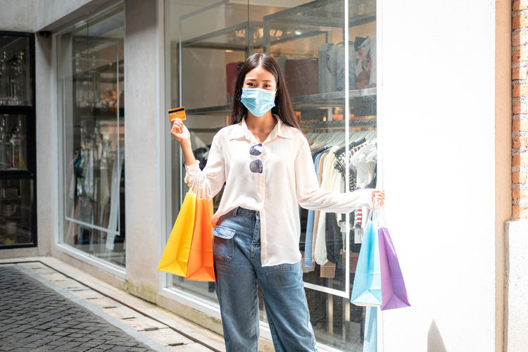 Woman holding umbrella standing at store