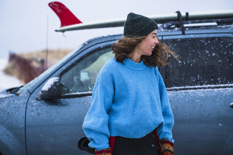 Young woman with umbrella standing in car during winter