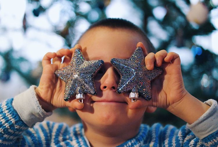 Portrait of kid holding christmas ornaments