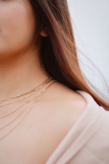 Midsection of young woman wearing necklace