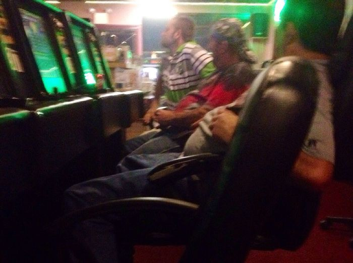 Enjoy The New Normal Like Father, Like Son, Like Best friend. Not sure what caught all three of their attention but something sure did. Leisure Activity Night Indoors  Illuminated Real People Men Nightlife One Person Gambling Casino Slot Machine People Adult