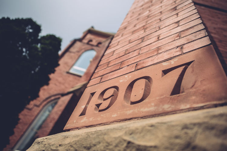Architecture Building Building Exterior Built Structure Capital Letter Close-up Communication Day Focus On Foreground Low Angle View Nature No People Number Old Outdoors Selective Focus Sign Sky Text Western Script