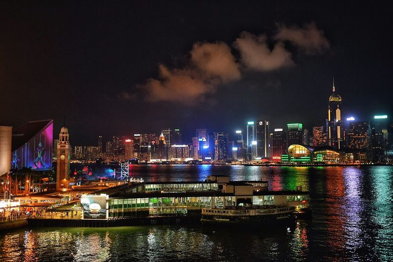 Illuminated cityscape at victoria harbour against sky at night