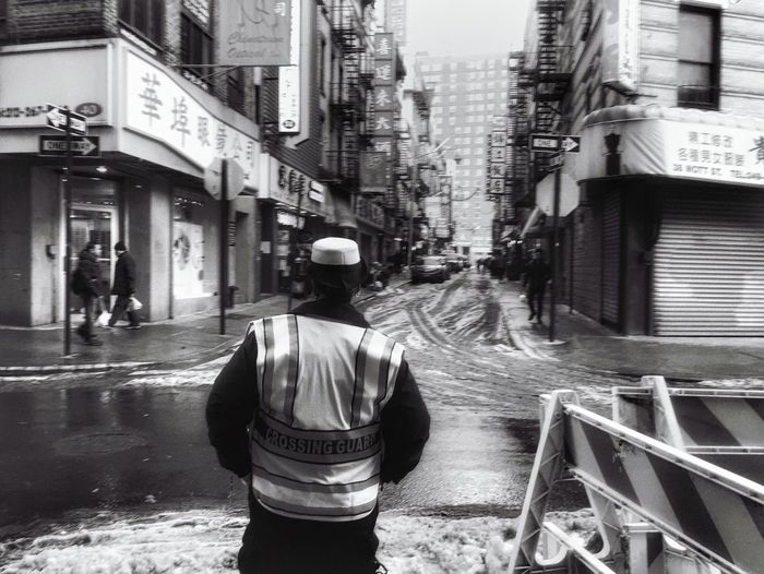 Rear view of man in reflective clothing standing on street during winter
