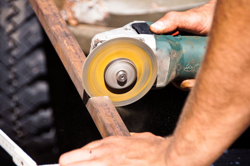 Close-Up Of Hands Cutting Metal With Angle Grinder