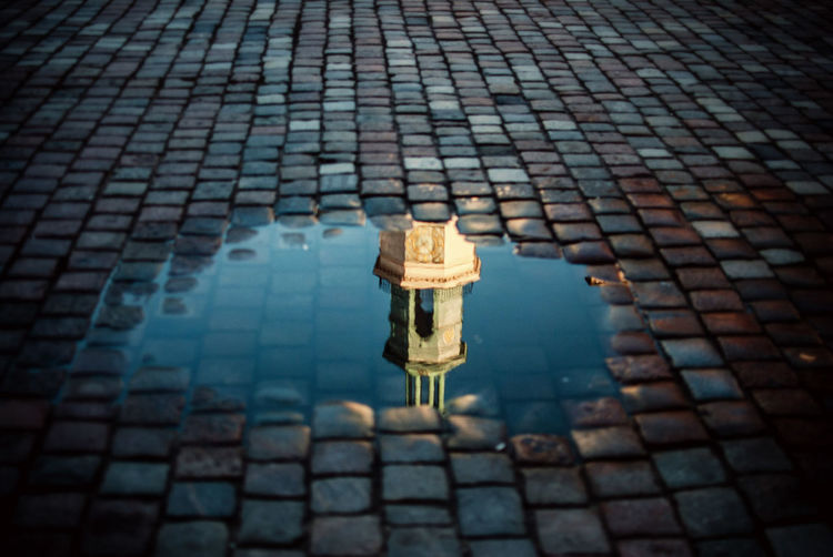 Clock Tower Of Poznan Town Hall Reflecting In Puddle On Street
