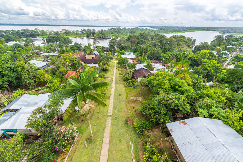View of Puerto Narino with the Amazon River in the background in Colombia Amazon Amazon Rainforest Amazon River Amazonas Colombia Day Foliage Green Jungle Landscape Leticia Nature No People Outdoors Puerto Nariño Rain Forest Rainforest Sky South America Tourism Town Travel Travel Destinations Tree Water
