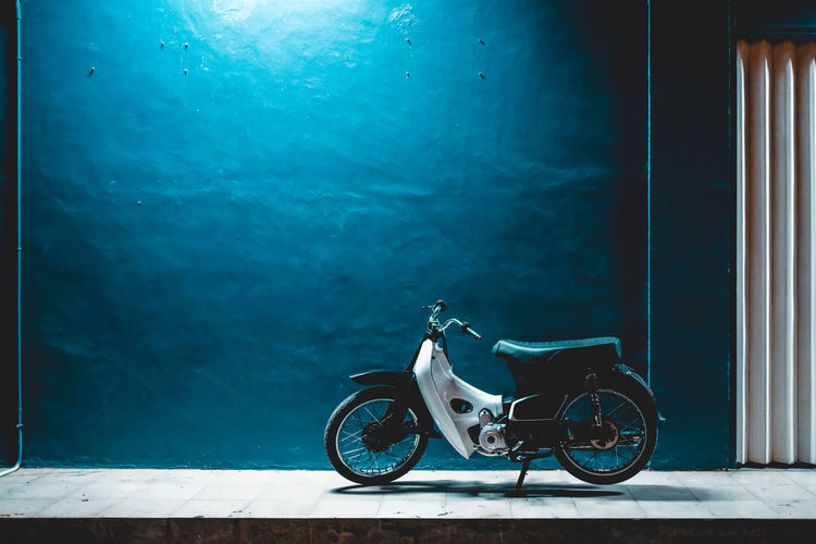 Motor Scooter Parked On Sidewalk Against Blue Wall At Night