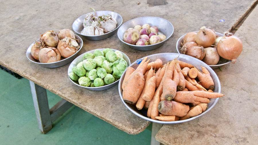 High Angle View Of Various Vegetables In Containers On Wooden Tables