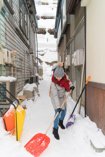Woman cleaning snow in alley