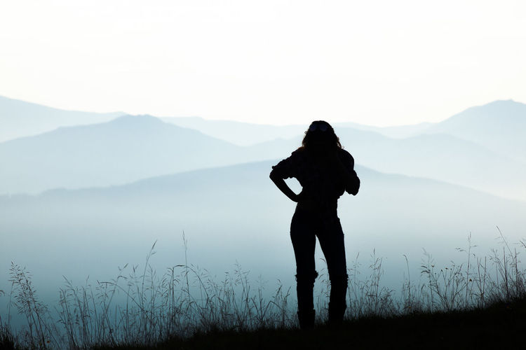 Silhouette woman standing on mountain against sky
