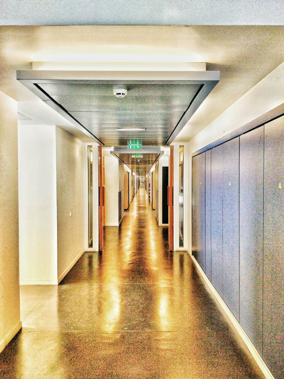 architecture, arcade, corridor, the way forward, direction, empty, indoors, building, illuminated, built structure, diminishing perspective, no people, flooring, ceiling, reflection, lighting equipment, absence, wall - building feature, vanishing point, long, light fixture, underground walkway