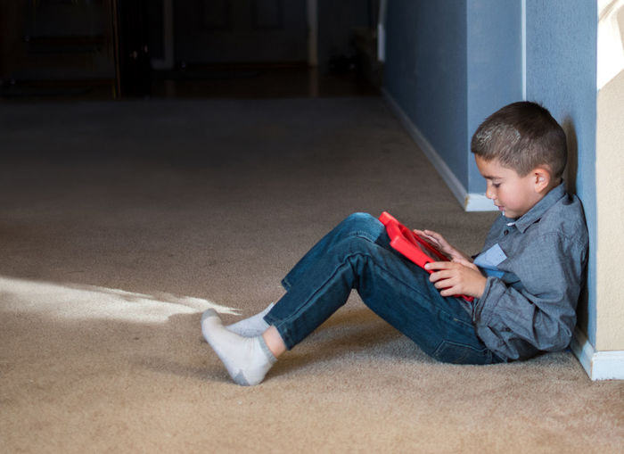 A young boy sits in the hall alone watching videos on his tablet