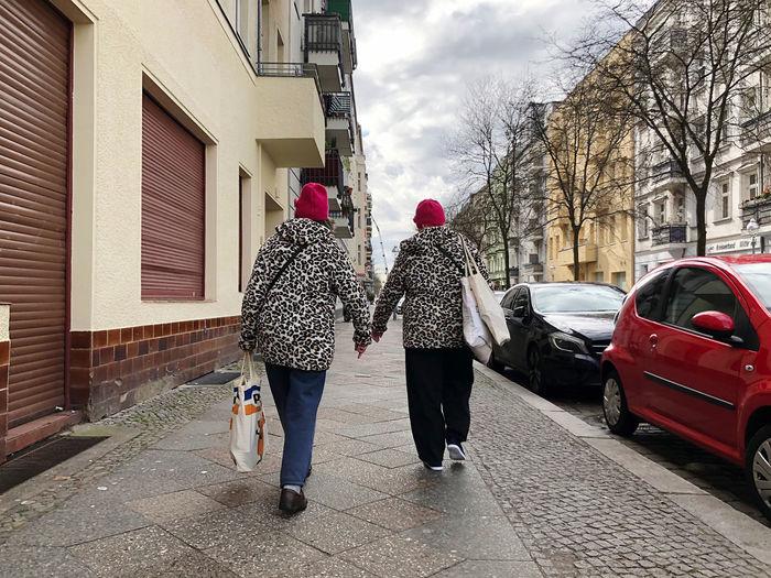 Rear view of women walking on footpath in city