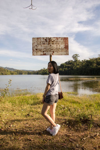 Side view of young woman standing by signboard on field against lake in forest