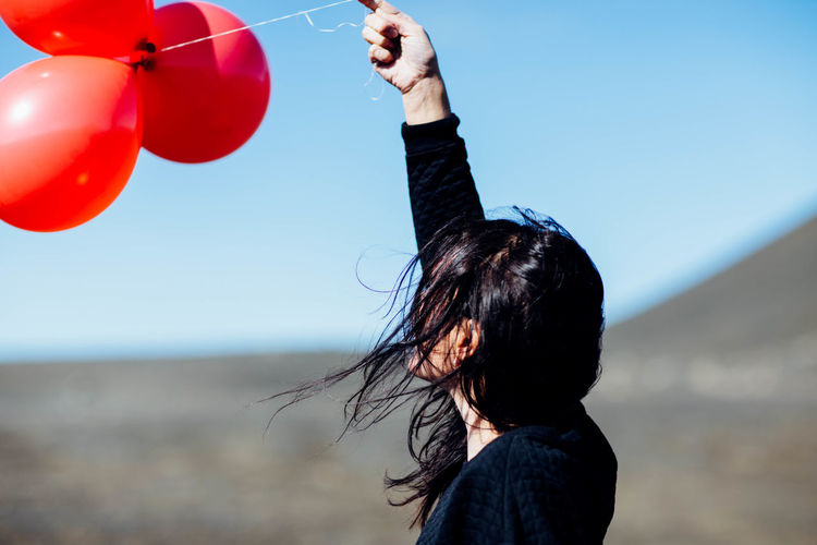 Side View Of Young Woman Holding Balloons At Beach