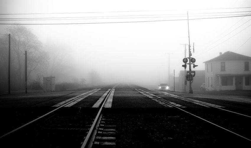 Small town railroad crossing in the early morning fog. Converging Lines Headlights Power Line  Foggy Truck Crossing Signals Parallel Lines Black & White Morning Light Early Morning Foggy Morning Railroad Crossing Crossing Sign Rail Transportation Mist Vehicle Light