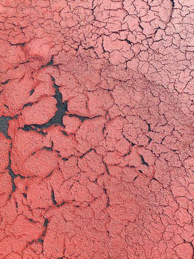 Full frame shot of cracked red asphalt