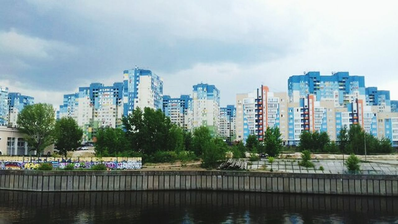 city, skyscraper, building exterior, architecture, urban skyline, cityscape, river, built structure, city life, downtown district, water, modern, development, travel destinations, tree, reflection, sky, outdoors, cloud - sky, waterfront, no people, apartment, day, nature