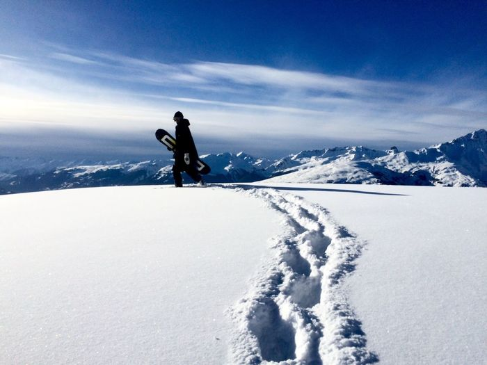 Man On Snowboarding On Snow Covered Mountain Against Sky