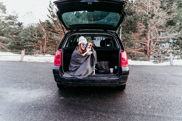 Woman holding dog while sitting in car trunk