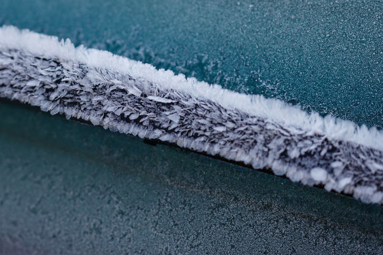 High angle view of frozen windshield wiper