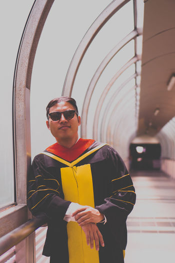 Portrait of young man wearing sunglasses and graduation gown while standing in corridor