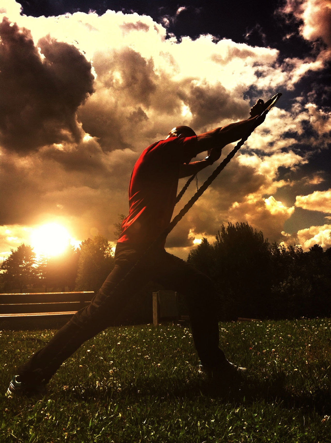 Side view of man doing exercises at sunset