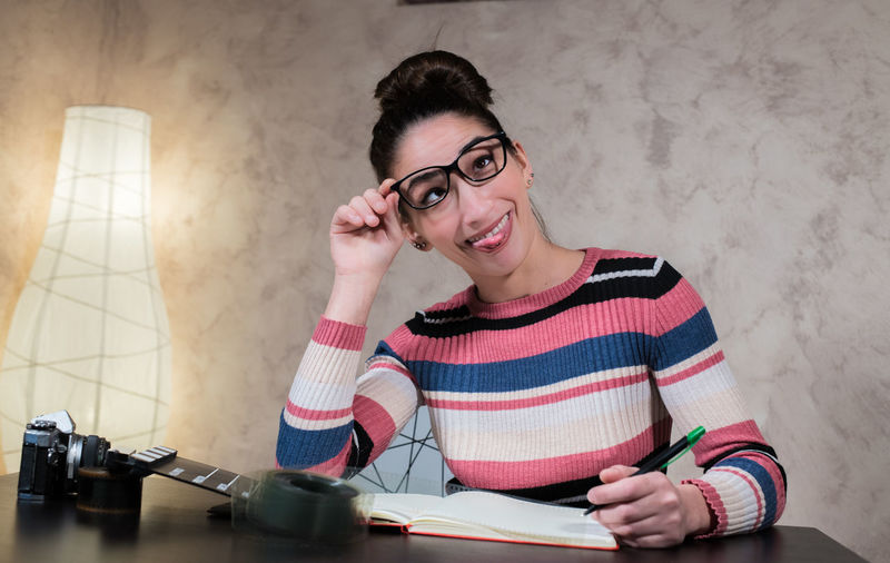 Young woman making face while writing on book at desk